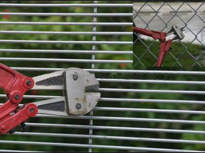 A red bolt cutter nips chain link fence, but cannot even stretch into small holes of 358 fence.