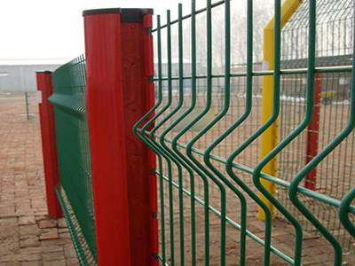 Green PVC coated 3D fence panels are installed in red and yellow peach posts.