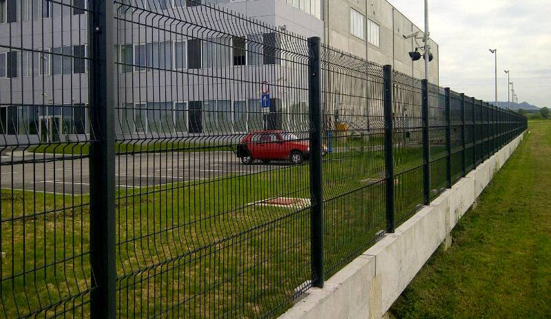 3D PVC coated fence is fixed upon concrete around a white building.