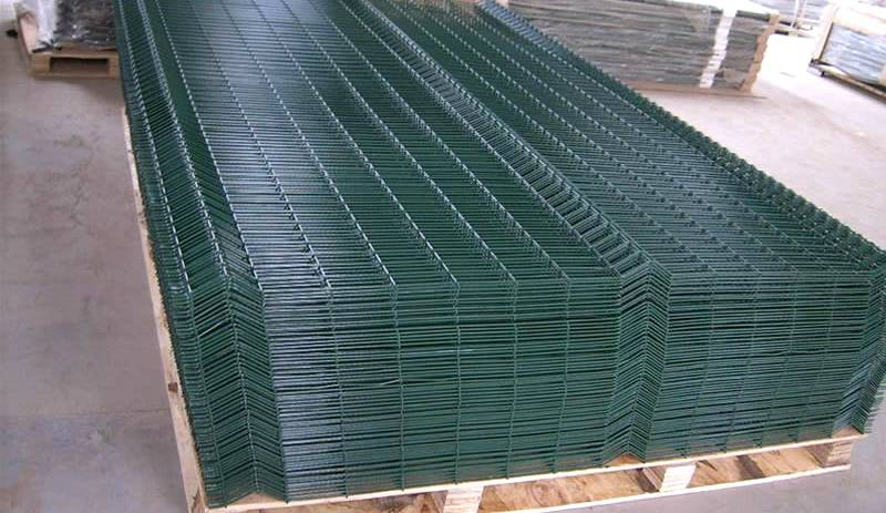 Green 3D fence panels are packed on the top of each other in a wooden pallet.