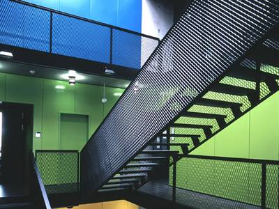 Black PVC coated expanded metal bannister rail guard used in a office, with colorful walls.