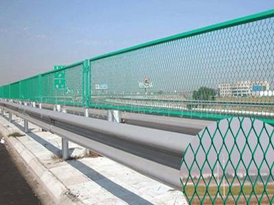Green PVC coated expanded metal highway fence used in a highway road.