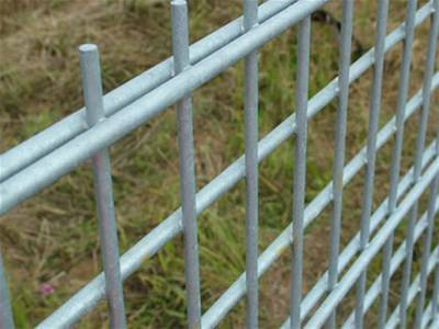 Galvanized double wire fence doubled horizontal wires at a distance.
