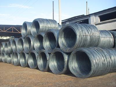 several rolls of galvanized wire is lying on earth.