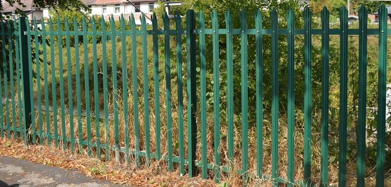 Green palisade fence is installed on the outside of houses and weeds, with pales being W-section and triple point head.