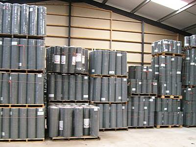 Welded wire lath panels packed in rolls, being put on wooden pallets, and stored in warehouse.