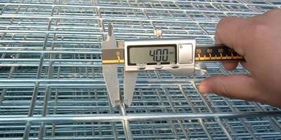 A electronic ruler is examining the wire mesh panel diameter.