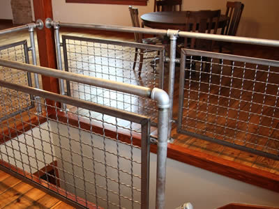 Woven crimped wire cloth infill panels with square holes are installed on fences of walkways indoors.